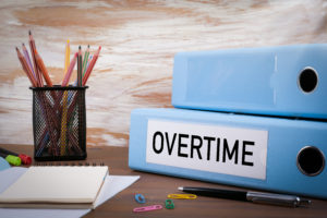 Overtime, Office Binder on Wooden Desk. On the table colored pencils, pen, notebook paper